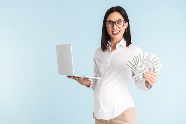 Wizerunek pięknej młodej kobiety w ciąży biznesu na białym tle przy użyciu komputera przenośnego, trzymając pieniądze.
