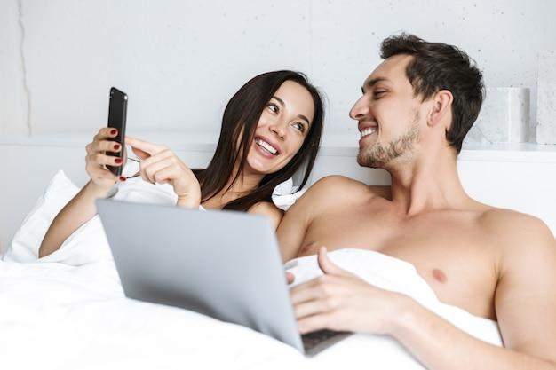 Wizerunek pięknej pary za pomocą laptopa i smartfona, leżąc w łóżku w domu lub apartamencie hotelowym