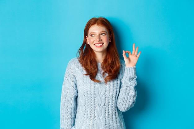 Wizerunek pięknej rudowłosej kobiety pokazującej dobry znak i uśmiechniętej zadowolonej, jak i zgadzam się, stojącej na niebieskim tle