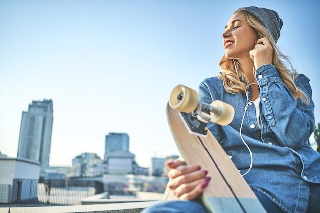 Wizerunek pięknej stylowej uśmiechniętej kobiety siedzącej na schodach ulicy