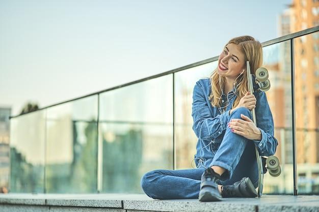Wizerunek pięknej stylowej uśmiechniętej kobiety słuchania muzyki siedzącej na schodach ulicy