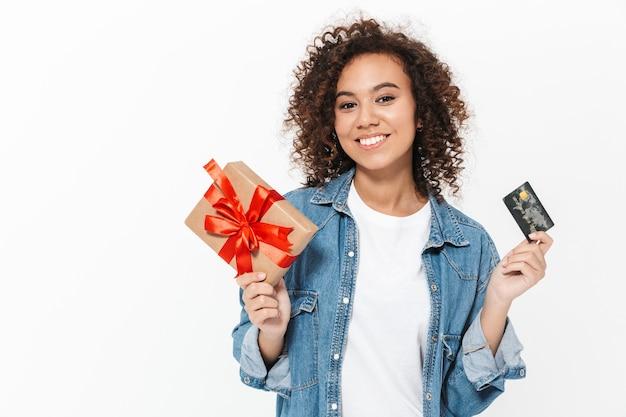Wizerunek pięknej szczęśliwej młodej afrykańskiej kobiety pozuje na białym tle nad białą ścianą, trzymając obecne pudełko i kartę kredytową.