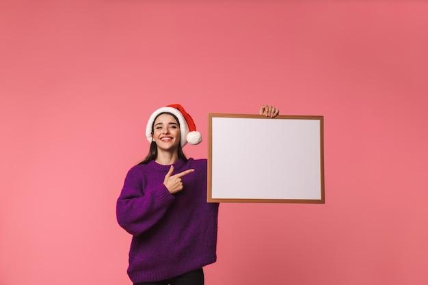 Wizerunek pięknej szczęśliwej młodej kobiety emocjonalne pozowanie na białym tle nad różowym trzymając copyspace puste wskazując.