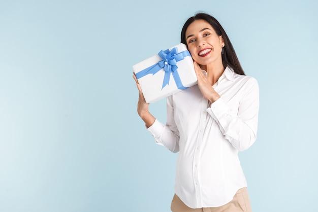 Wizerunek pięknej szczęśliwej młodej kobiety w ciąży na białym tle gospodarstwa pudełko.