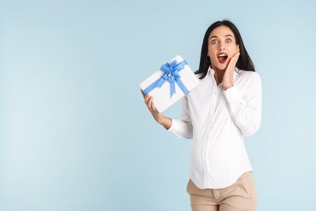 Wizerunek pięknej zszokowanej młodej kobiety w ciąży na białym tle, trzymając pudełko.
