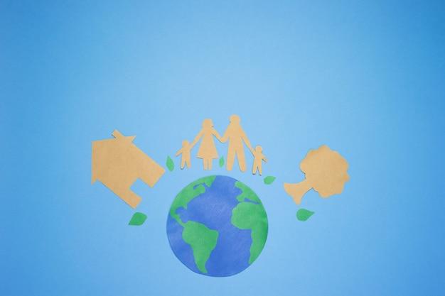 Wizerunek planety ziemia na błękitnym tle. wycinanka z papieru rodzinnego i drzewa
