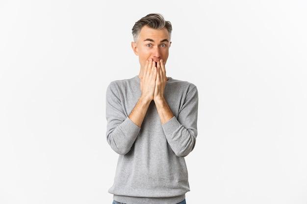 Wizerunek podekscytowany i rozbawiony kaukaski mężczyzna z siwymi włosami, zakryte usta