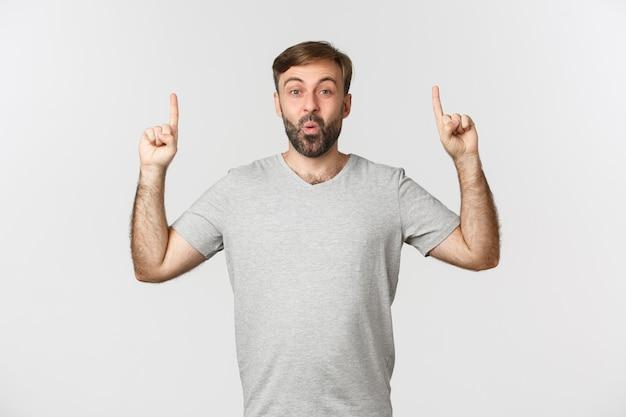 Wizerunek podekscytowany przystojny mężczyzna w szarej koszulce