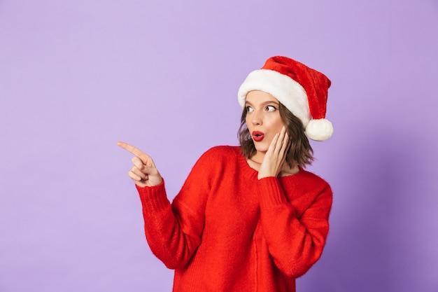 Wizerunek podekscytowany zszokowany młoda kobieta ubrana w boże narodzenie kapelusz na białym tle nad wskazując fioletową ścianą.
