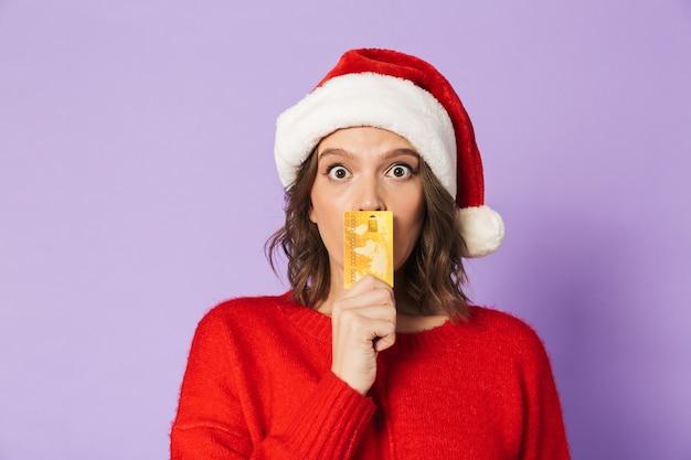Wizerunek podekscytowany, zszokowany młoda kobieta ubrana w świąteczny kapelusz na białym tle nad fioletową ścianą, trzymając kartę debetową.