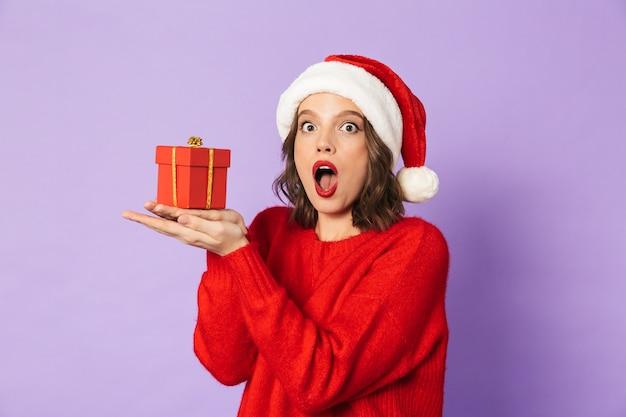 Wizerunek podekscytowany zszokowany młoda kobieta ubrana w świąteczny kapelusz na białym tle nad fioletową ścianą, trzymając pudełko niespodzianka.