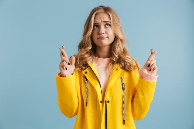Wizerunek poważnej kobiety po dwudziestce w żółtym płaszczu przeciwdeszczowym trzymającej kciuki