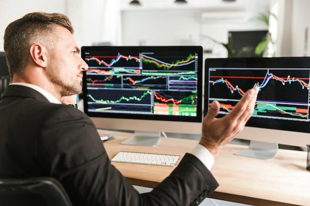 Wizerunek poważnych biznesmen 30s ubrany w garnitur pracy w biurze i patrząc na komputerze z grafiką i wykresami na ekranie