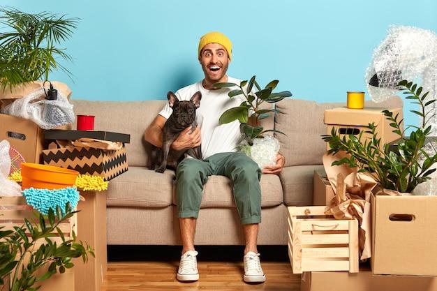 Wizerunek pozytywnego modnego faceta wynajmującego nowe mieszkanie, mieszka z ulubionym psem