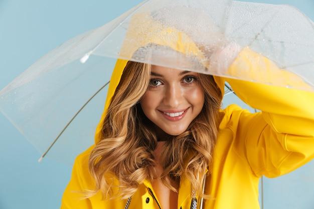 Wizerunek pozytywnej kobiety lat dwudziestych w żółtym płaszczu przeciwdeszczowym stojącej pod przezroczystym parasolem
