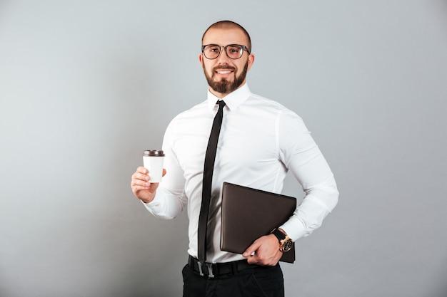 Wizerunek pracujący biznesmen trzyma takeaway kawę i laptop w rękach w szkłach i kostiumu, odizolowywający nad szarości ścianą