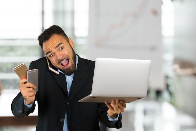 Wizerunek pracuje na jego laptopie amerykanina afrykańskiego pochodzenia biznesmen. przystojny młody mężczyzna
