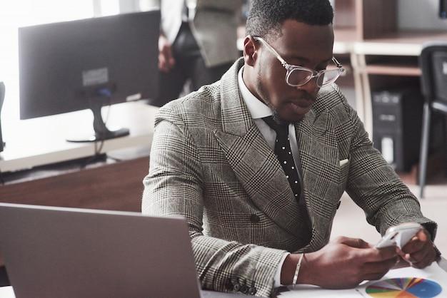 Wizerunek pracuje na jego laptopie amerykanina afrykańskiego pochodzenia biznesmen