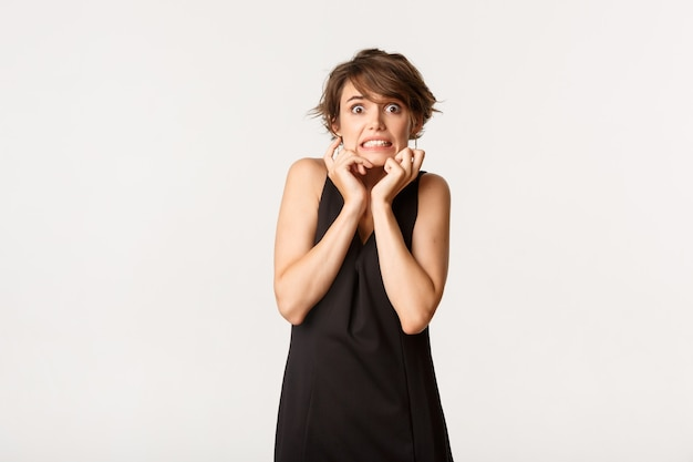 Wizerunek przerażonej, nieśmiałej dziewczyny w czarnej sukni, wyglądającej na przestraszoną i drżącą ze strachu, stojącej nad bielą.