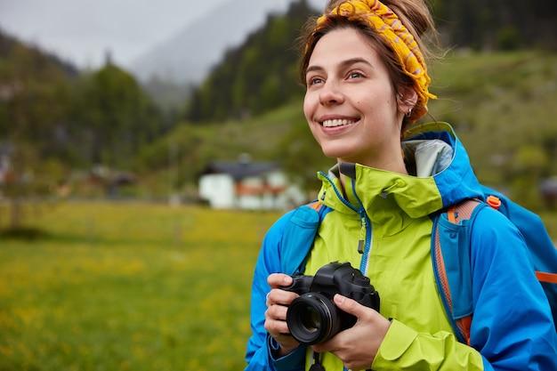 Wizerunek przyjemnie wyglądającej wesołej kobiety ubranej niedbale, posiada profesjonalny aparat