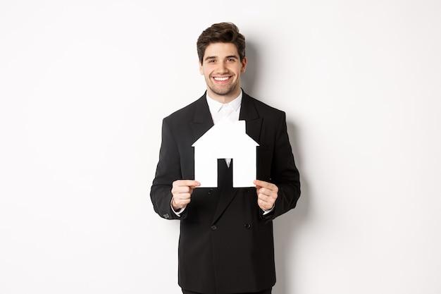Wizerunek przystojnego agenta nieruchomości w czarnym garniturze pokazującym maket domu, uśmiechając się do kamery, stojąc na białym tle.