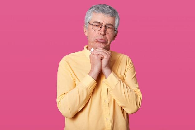 Wizerunek przystojnego dojrzałego mężczyzny ze zmarszczkami na twarzy, obrażony wyraz twarzy, stojący z obleśnymi ustami, odczuwa smutek