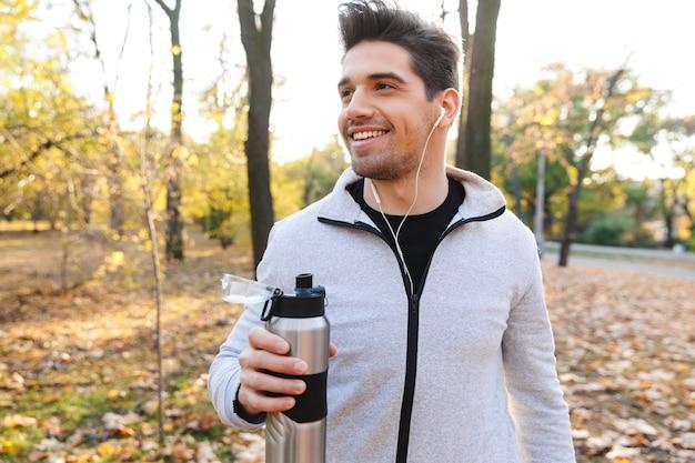 Wizerunek przystojnego emocjonalnego młodego sportowca na świeżym powietrzu w parku, słuchanie muzyki przez słuchawki wody pitnej.