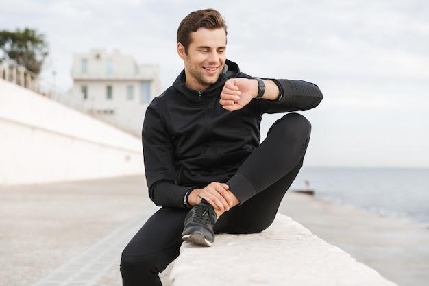 Wizerunek przystojnego faceta lat 30. w czarnej odzieży sportowej, patrząc na zegarek, siedząc na promenadzie nad morzem