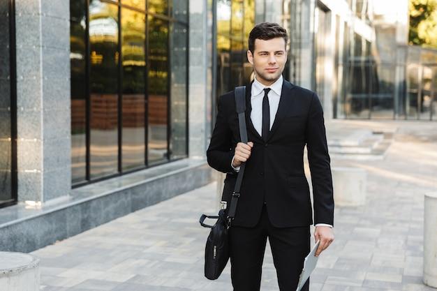 Wizerunek przystojnego młodego biznesmena spaceru na zewnątrz w pobliżu centrum biznesowego ze schowka.