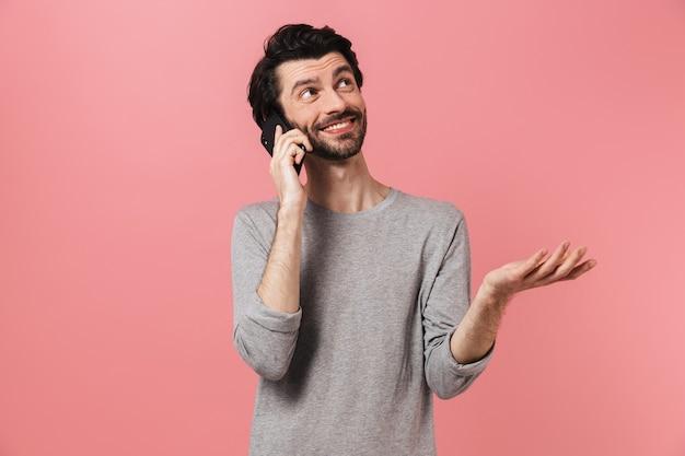 Wizerunek przystojnego młodego człowieka na różowej ścianie rozmawia przez telefon komórkowy.
