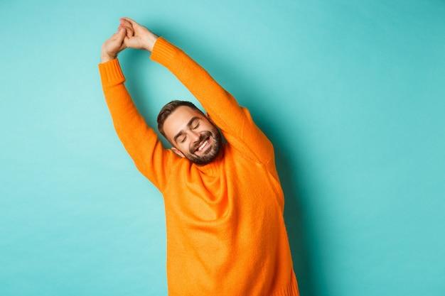 Wizerunek przystojnego młodzieńca wyciągającego ręce i uśmiechającego się po dobrym odpoczynku, stojącego w pomarańczowym swetrze na jasnoniebieskiej ścianie.