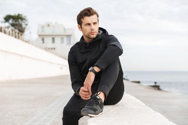 Wizerunek przystojnego sportowego mężczyzny 30-tych w czarnej odzieży sportowej, siedzącego na promenadzie nad morzem