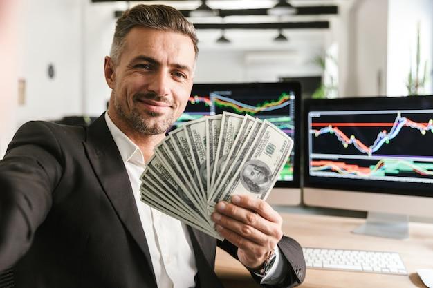 Wizerunek przystojny biznesmen 30s ubrany w garnitur trzyma wentylator pieniędzy podczas pracy w biurze z grafiką i wykresami na komputerze