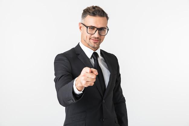 Wizerunek przystojny biznesmen na białym tle nad białą ścianą, wskazując na pozowanie.
