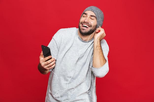 Wizerunek przystojny mężczyzna 30s słuchanie muzyki za pomocą słuchawek i telefonu komórkowego, na białym tle