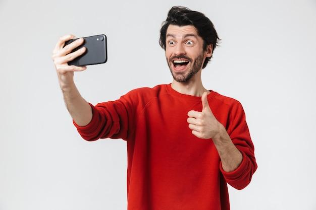 Wizerunek przystojny, młody, podekscytowany mężczyzna pozuje na białej ścianie weź selfie przez telefon komórkowy pokazując kciuk do góry.