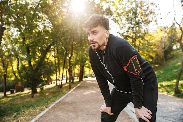 Wizerunek przystojny młody sport fitness biegacz mężczyzna na zewnątrz w parku słuchanie muzyki ze słuchawkami.