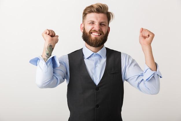 Wizerunek przystojny podekscytowany młody brodaty mężczyzna stojący na białym tle nad białą ścianą zrobić gest zwycięzcy.