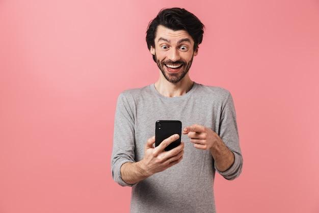 Wizerunek przystojny podekscytowany szczęśliwy zszokowany młody człowiek na różowej ścianie za pomocą telefonu komórkowego.