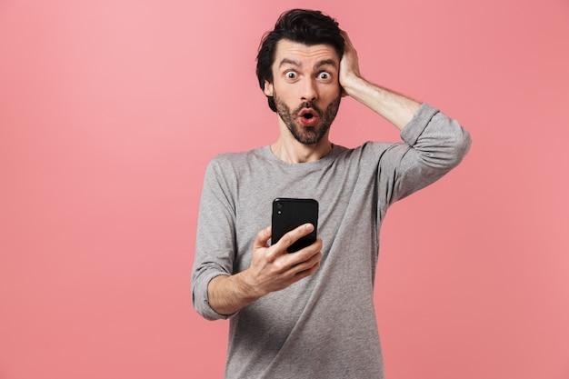 Wizerunek przystojny podekscytowany zszokowany młody człowiek na różowej ścianie za pomocą telefonu komórkowego.