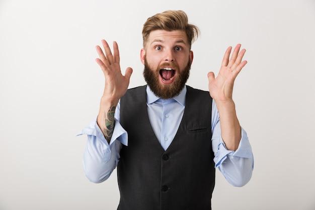 Wizerunek przystojny zszokowany podekscytowany młody brodaty mężczyzna stojący na białym tle nad białą ścianą.