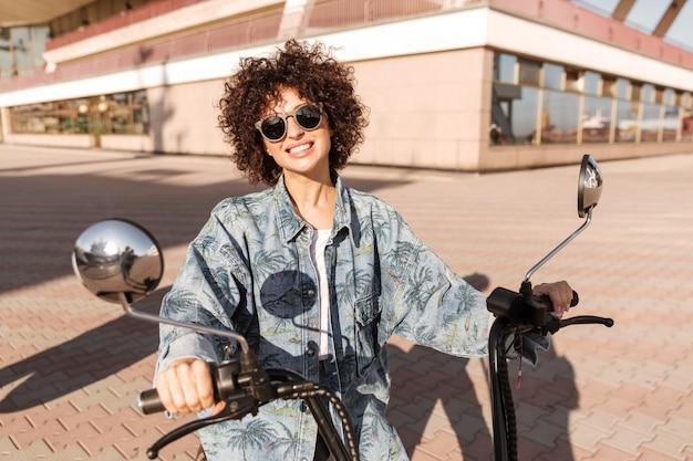 Wizerunek radosna kędzierzawa kobieta siedzi na motocyklu w okularach przeciwsłonecznych