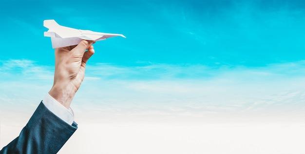 Wizerunek ręki trzymającej papierowy samolot. koncepcja turystyki.