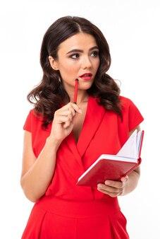 Wizerunek rozważnej uroczej brunetki w czerwonej sukience na białej ścianie