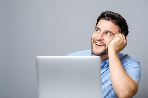 Wizerunek rozważny mężczyzna ubierał w błękitnej koszula używać laptop