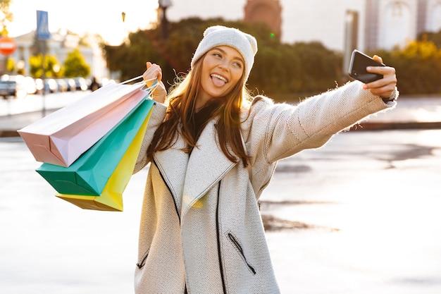 Wizerunek rudowłosej szczęśliwej kobiety spaceru na świeżym powietrzu, trzymając torby na zakupy, zrobić selfie przez telefon komórkowy.