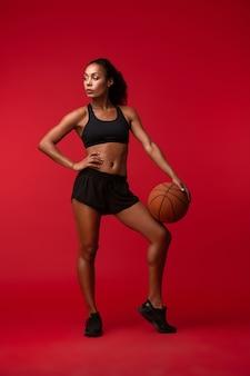 Wizerunek silnego młodego afrykańskiego sportowca fitness kobieta koszykarz pozowanie na białym tle nad czerwoną ścianą trzymającą piłkę.
