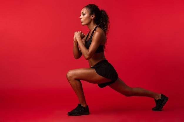 Wizerunek silnej młodej kobiety fitness afrykańskiego sportu pozowanie na białym tle na czerwonej ścianie ściany wykonać ćwiczenia.