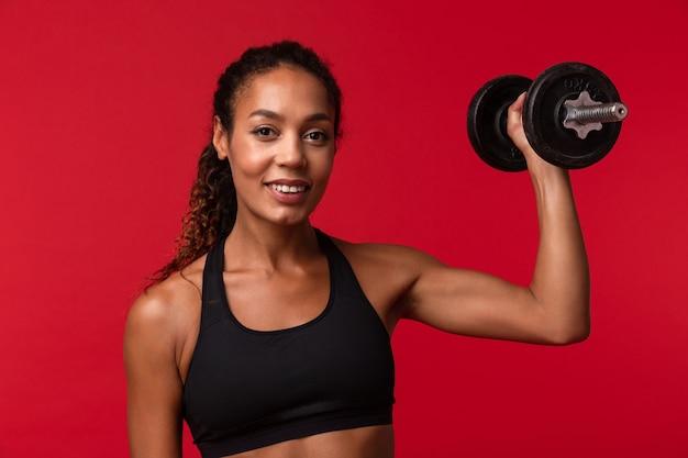 Wizerunek silnej młodej kobiety fitness afrykańskiego sportu pozowanie na białym tle na czerwonej ścianie ściany wykonywać ćwiczenia z hantlami.