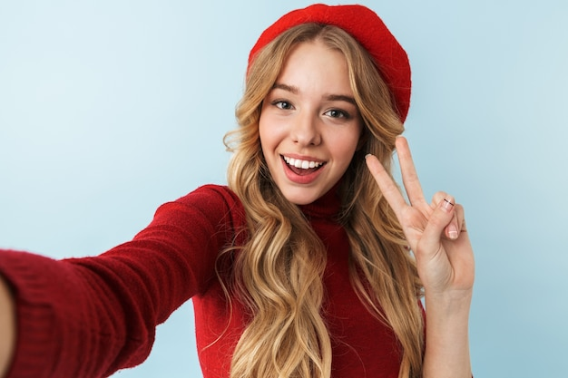 Wizerunek skromnej blond kobieta lat dwudziestych ubrana w czerwony beret, uśmiechając się podczas robienia zdjęcia selfie, na białym tle